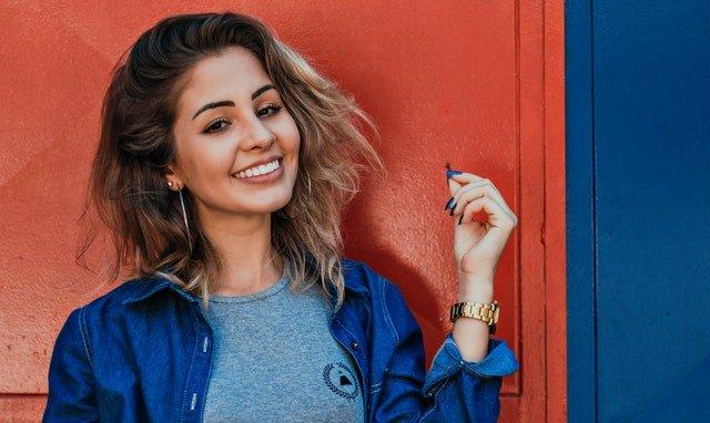 Usmiata mladá žena v ležérnom sivom tričku a rifľovej mikine.jpg