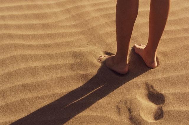 Osoba s bosými nohami stojaca v piesku.jpg