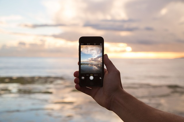Mobil v ruke, more, západ Slnka.jpg