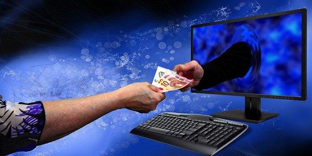 Monitor a klávesnica, ruka podáva peniaze.jpg